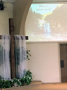 Front of sanctuary where a cross stands with a thorn crown and white cloth draped over it below a screen depicting a waterfall.